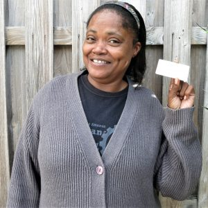 A client shows of her smile, and her new ID card