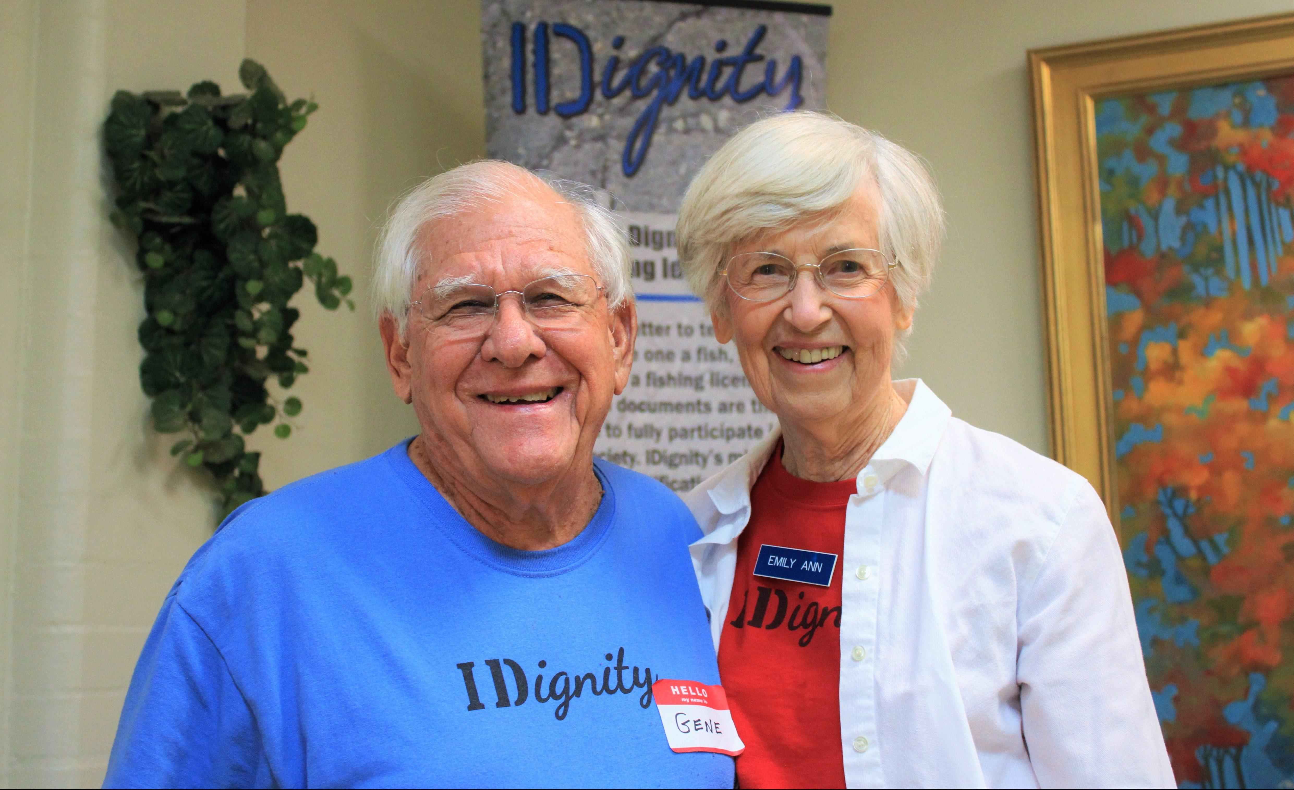 An elderly volunteer couple smile for the camera while serving food to volunteers in the hospitality room at an Identification Clinic