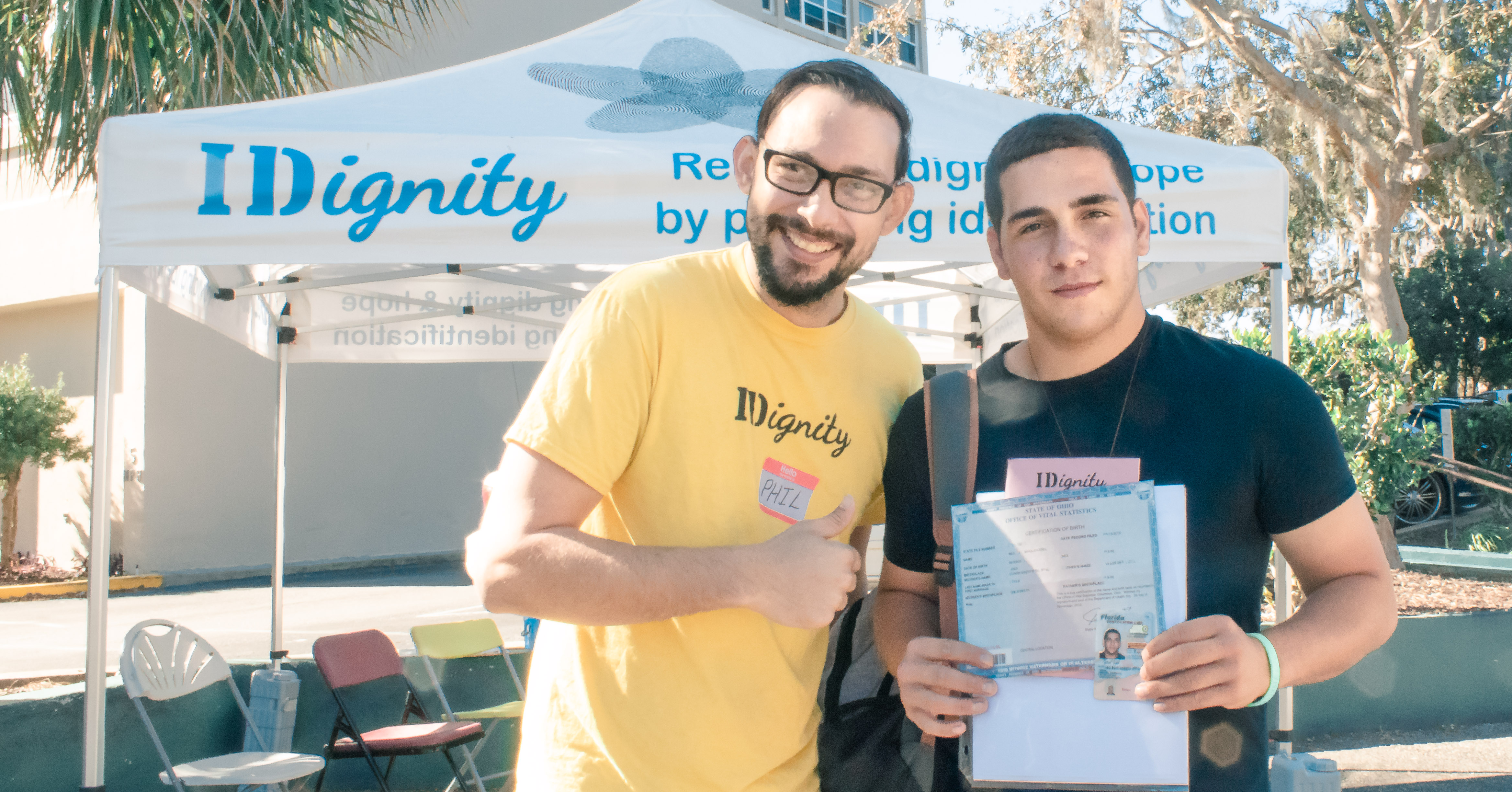 IDignity Client shows off his new birth certificate and ID to a volunteer, and the camera.