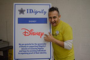 Disney volunteer Jose poses with Disney's sponsorship sign