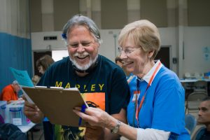 A volunteer signs in a client to the out-of-state birth certificates station clipboard.