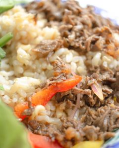 Close up of a taco bowl with rice, peppers, onions, and shredded beef.