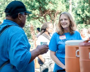 IDignity volunteer Robin greets a client with a smile and a cup of lemonade.