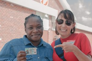 A client celebrates their new ID with a volunteer