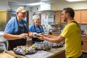 Ron and Barb serve up a delicious sandwich, provided by AdventHealth, to a hungry volunteer.