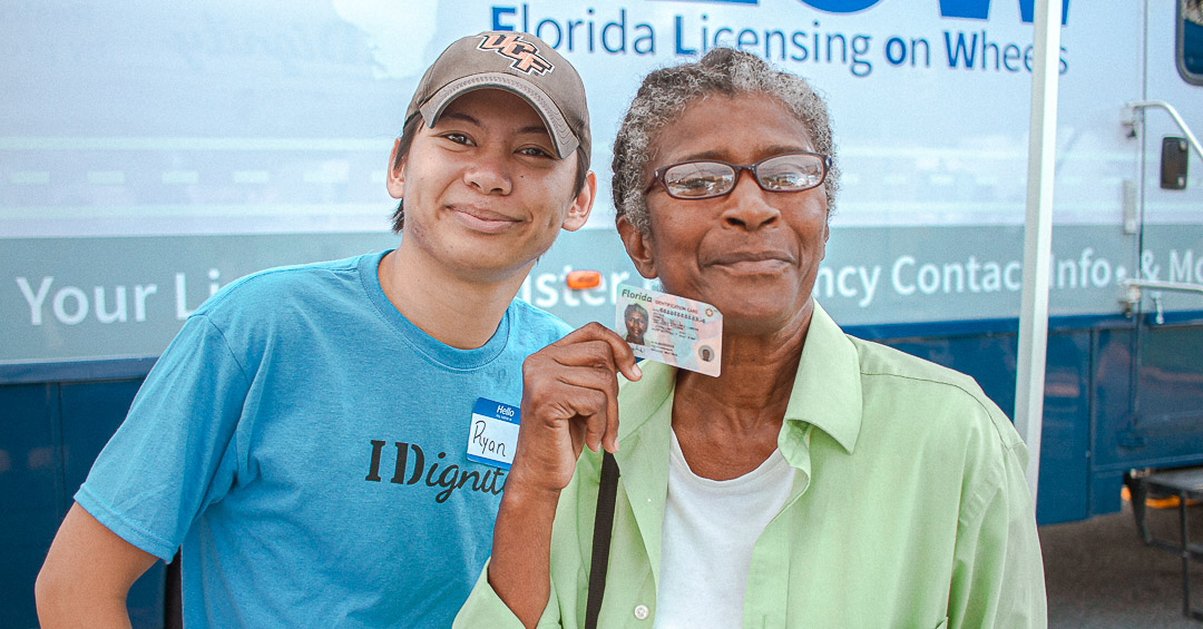 A client celebrates getting a new ID with an IDignity volunteer