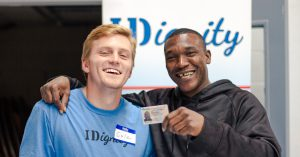 A client poses with his new ID and his favorite IDignity volunteer