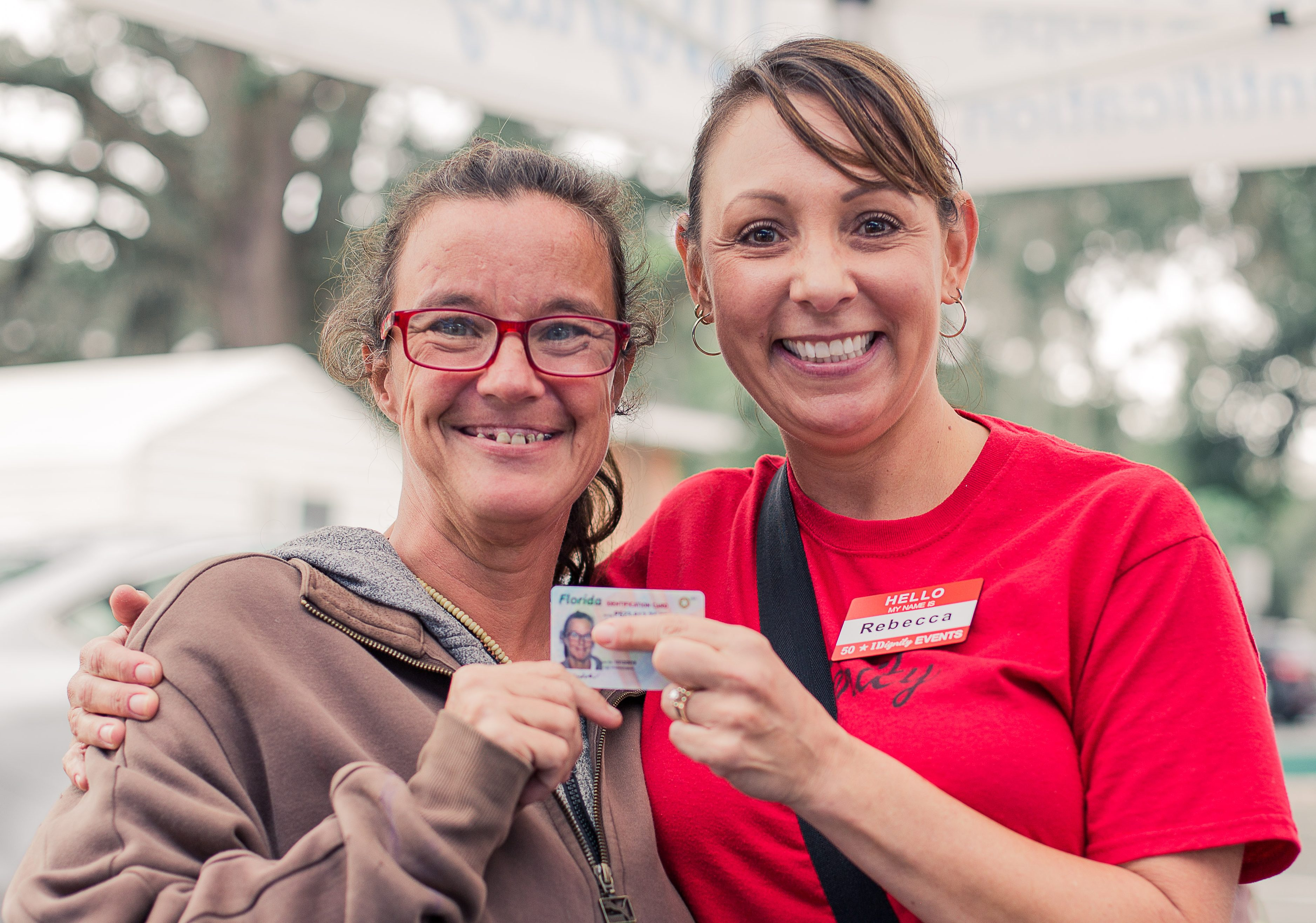 A happy client celebrates her new ID with an IDignity volunteer