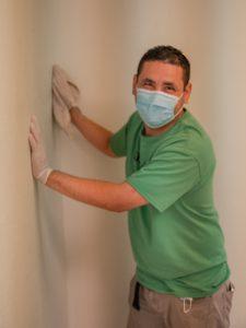 A volunteer washing the walls