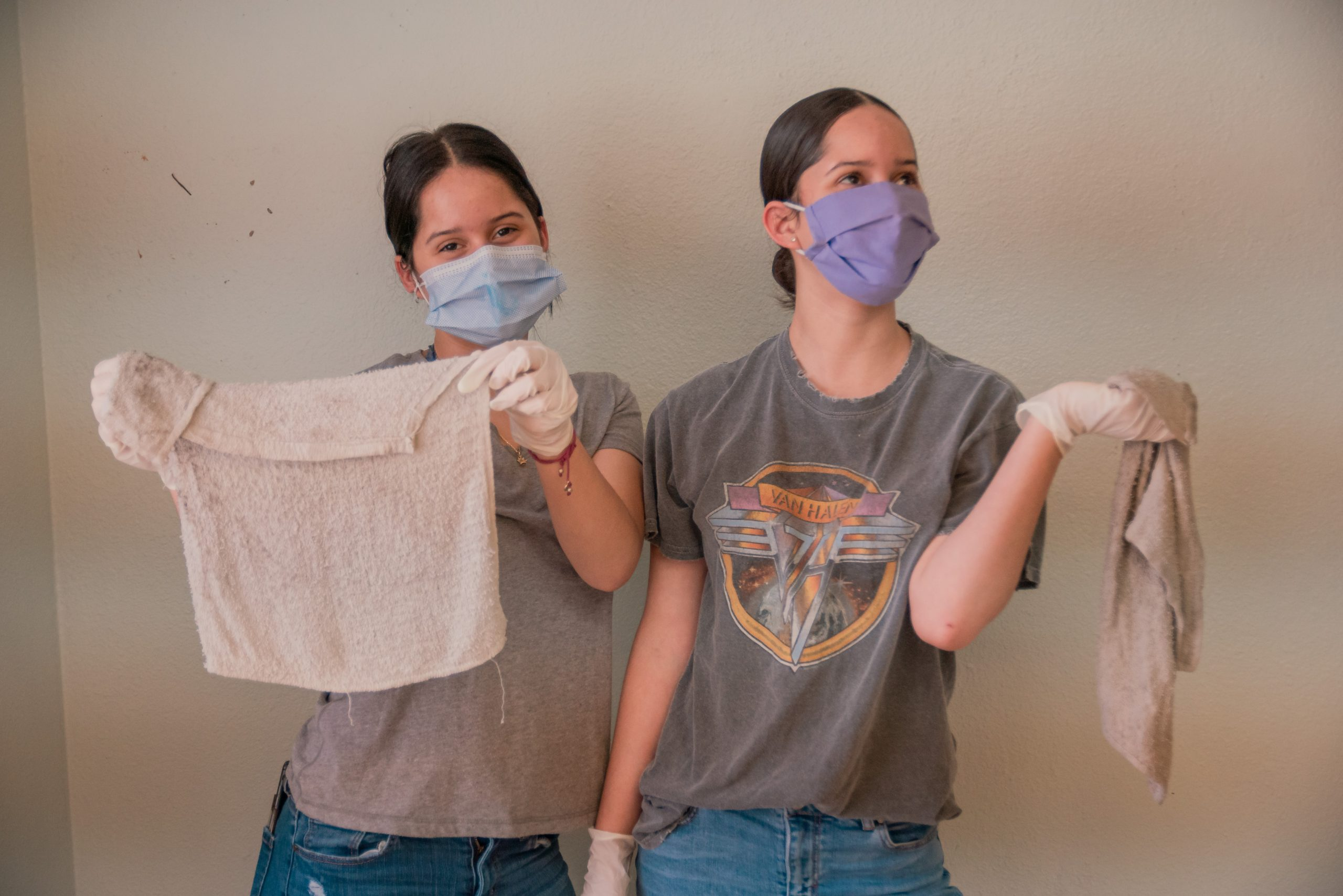 Two volunteers pose for the camera with their masks and cleaning supplies