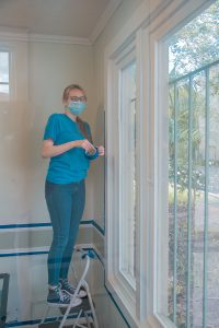 A volunteer taping the walls for painting