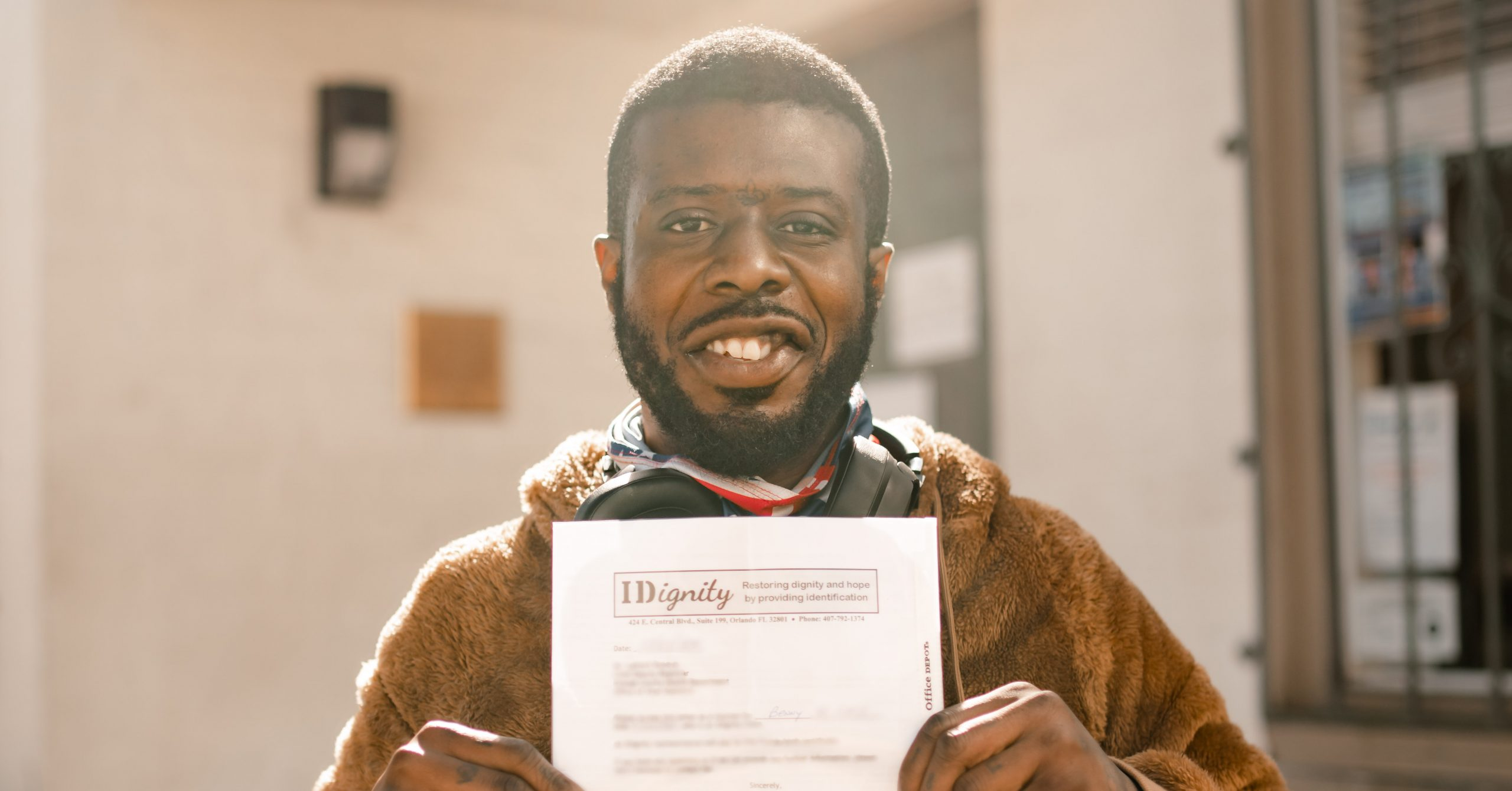 IDignity client Benny holds up the voucher that will help him get his Florida birth certificate.