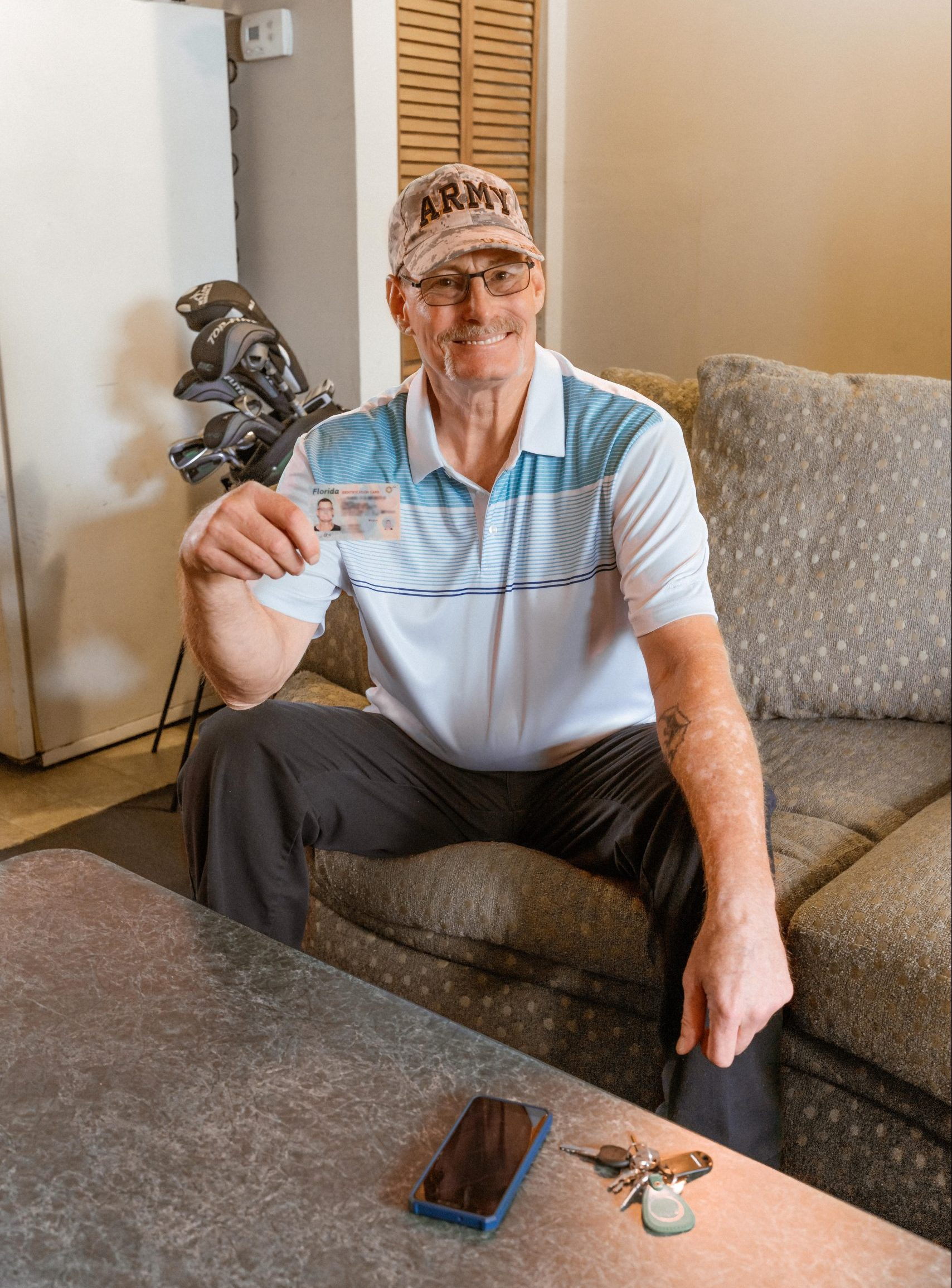IDignity client Chris, on his couch in his apartment with the ID that made it possible.